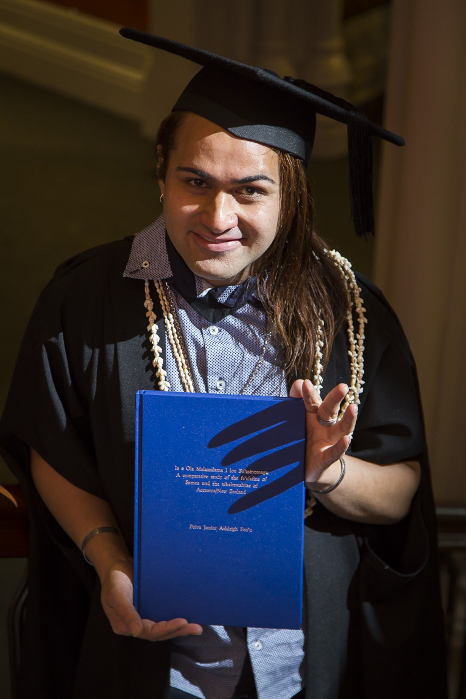2014 Master of Arts graduation ceremony holding my thesis.